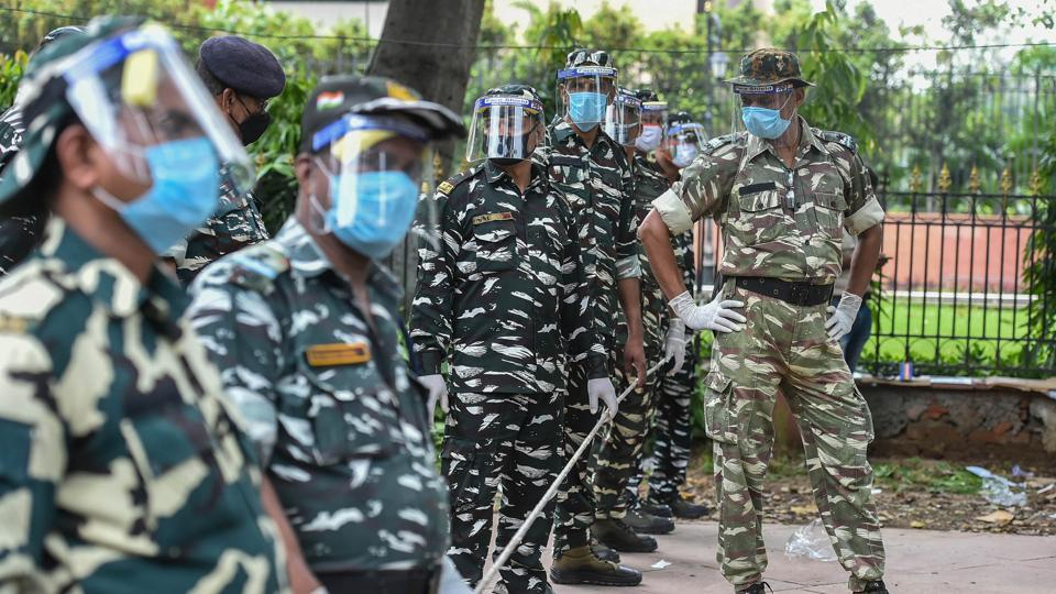 Security personnel with face shields and gloves stand guard outside Shastri Bhawan during a protest by Delhi Congress workers against the education ministry, in New Delhi, Friday.