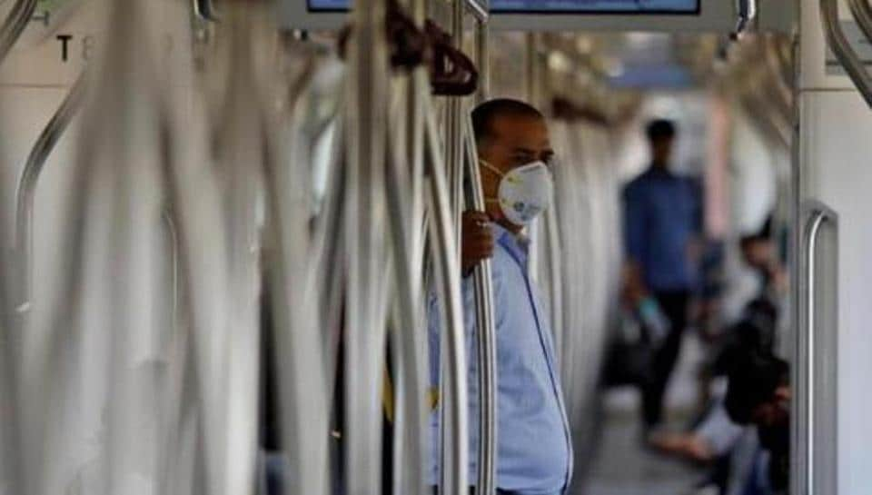 A commuter wearing a mask travels in a metro amid coronavirus fears, in New Delhi, India.