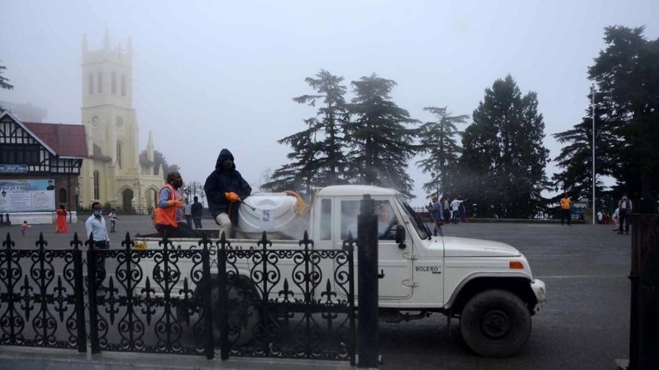 Municipal corporation workers sanitise The Ridge in Shimla on Sunday.