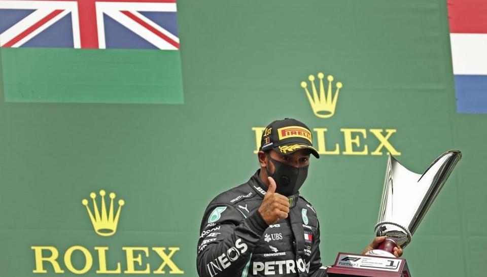 Mercedes driver Lewis Hamilton of Britain gives the thumbs up as he holds his trophy on the podium after placing first in the Formula One Grand Prix at the Spa-Francorchamps racetrack in Spa, Belgium, Sunday, Aug. 30, 2020. (AP Photo/Francisco Seco, Pool)
