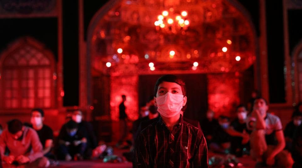 An Iranian Shiite Muslim boy wears a mask as he takes part in a mourning ceremony ahead of Ashura, the holiest day on the Shi'ite Muslim calendar, amid the spread of the coronavirus disease in northern Tehran.