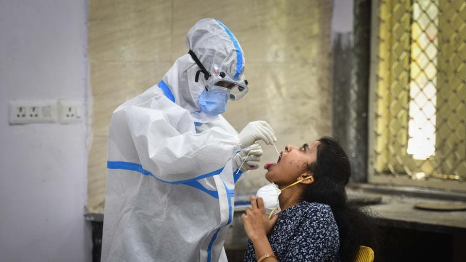 A healthcare worker collects a swab sample from a woman for coronavirus testing, in New Delhi on Friday.