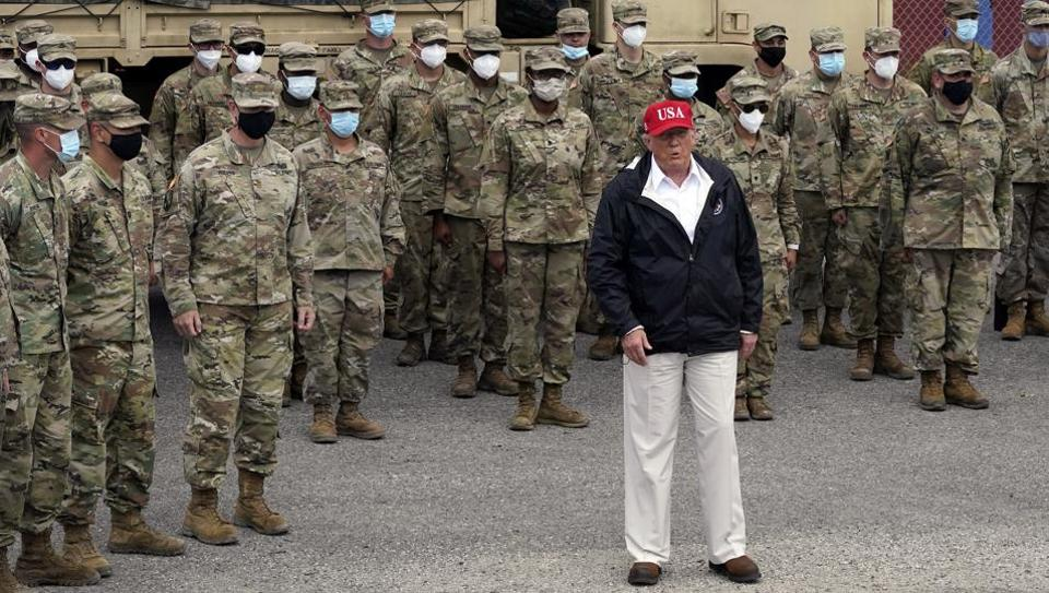 President Donald Trump stands with members of the Louisiana National Guard helping with recovery efforts from Hurricane Laura, Saturday.