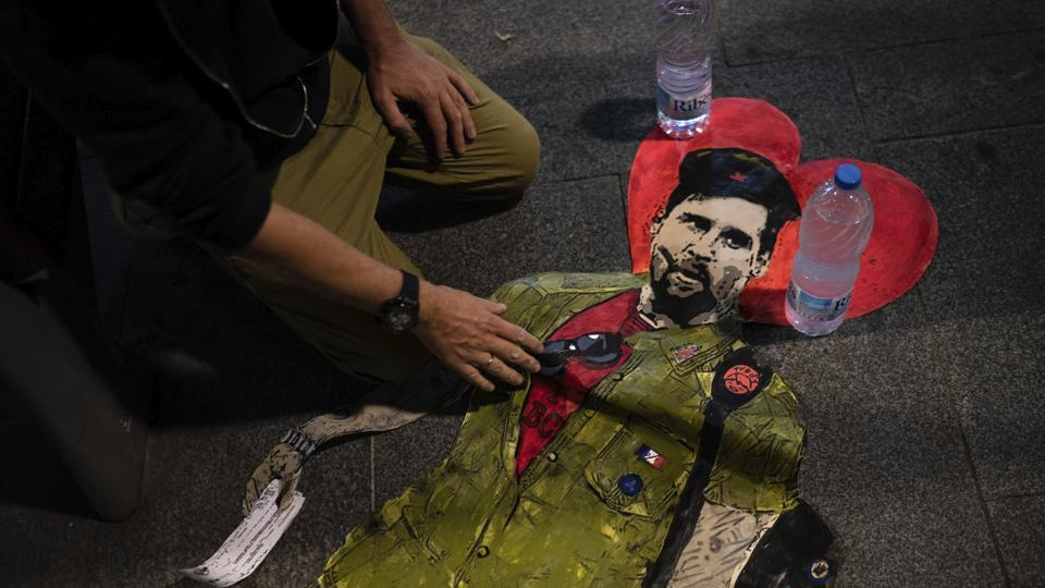 Artist TVBOY prepares to glue a painting depicting soccer player Lionel Messi dressed like Che Guevara named