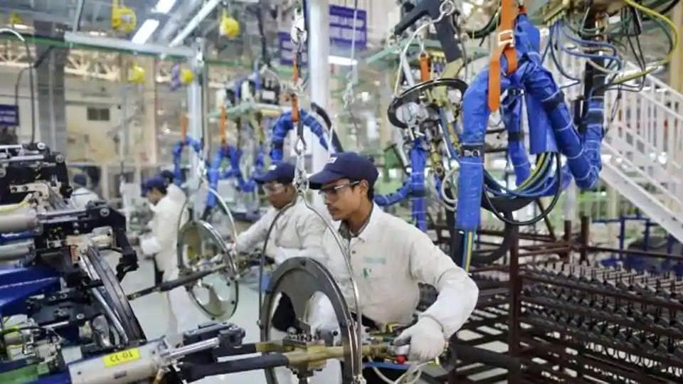 Employees work at the assembly line of the Honda Amaze car inside the company's manufacturing plant in Tapukara, Rajasthan.