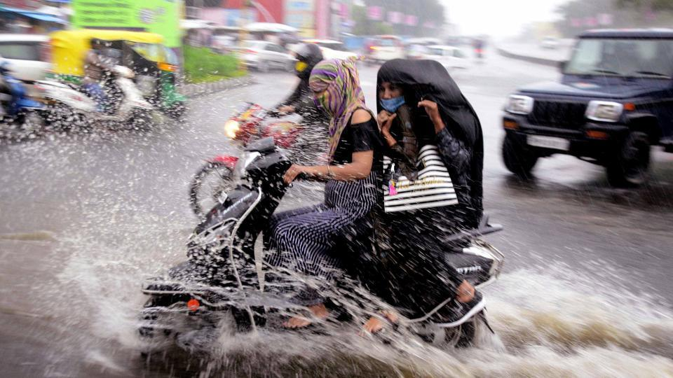 Commuters ride a bike on a waterlogged road during heavy rain in Bhopal.