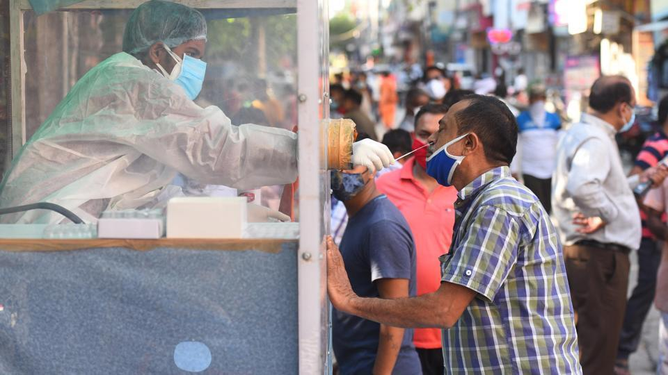 A health official collects a swab sample from a coronavirus testing kiosk set at a weekly market in Pandav Nagar, in New Delhi.