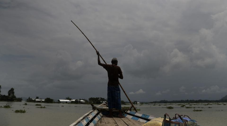 An Indian man rows a boat through floodwaters in Gagolmari village, Morigaon district, Assam, India.