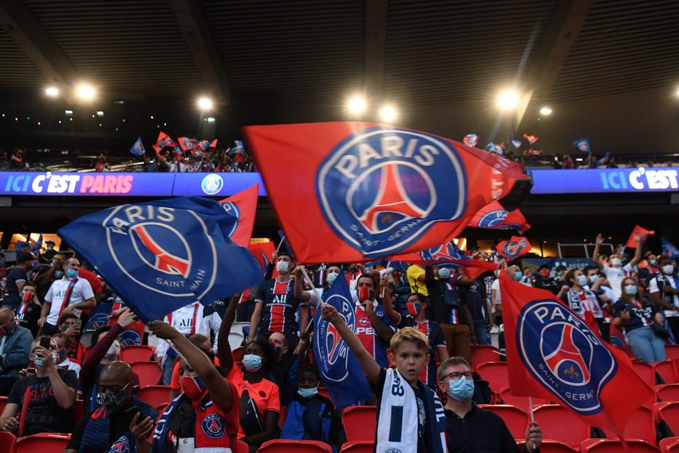 Paris Saint-Germain (PSG) supporters cheer for their team as they watch at the Parc des Princes.