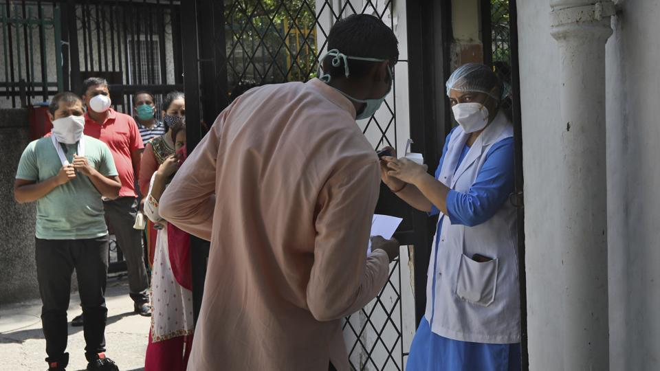 A health worker explains the working of an oximeter to a coronavirus patient to monitor his oxygen level in New Delhi on September 1, 2020. This third round of the survey will be conducted between September 1 and 7. (Manish Swarup / AP)