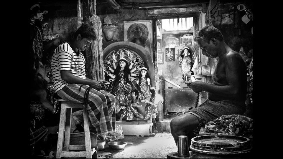 Idol makers at Kumortuli-- presumably the only neighbourhood of idol-makers in the world, braid jute hair to put finishing touches to idols just before the grand Durga Puja festival in Kolkata. (Manjit Singh Hoonjan)