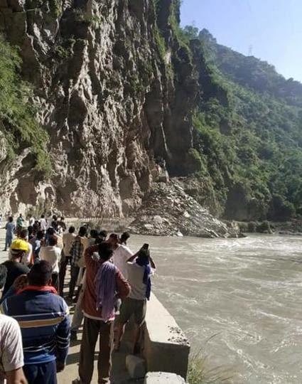 People watching the landslide on the Mandi-Kullu highway on Saturday morning.