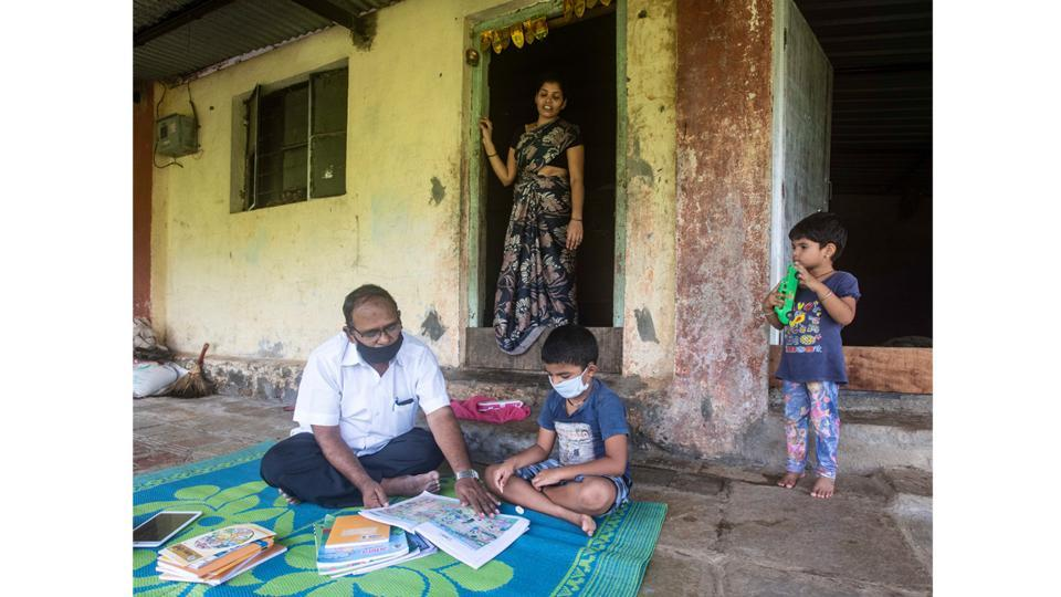 Anil Rathod (L), an assistant teacher at the Zila Parishad school teaches Shlok Sangale (R), a Class 1 student at the latter's residence as his mother and sister look on, at Kalamshet village, in Mulshi Taluka, Pune on September 4. Virtual classes are the new normal these days, but online classes are out of bounds for children in rural areas. This has not stopped the teachers of Zila Parishad from taking education to their children. (Pratham Gokhale / HT Photo)