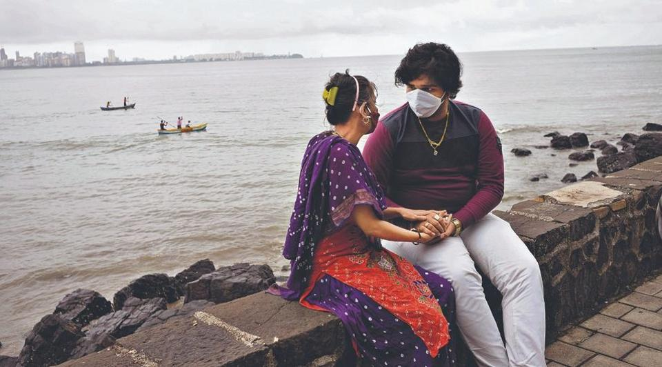 A masked couple sits by the Arabia Sea in Mumbai.
