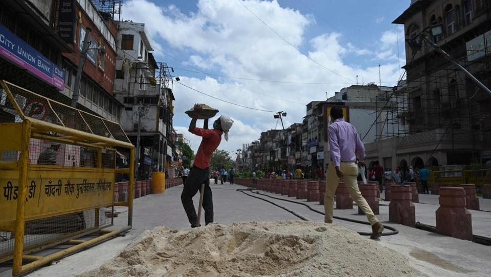 A labourer working in a construction site prepares to carry sand along a street in New Delhi on August 31, 2020.