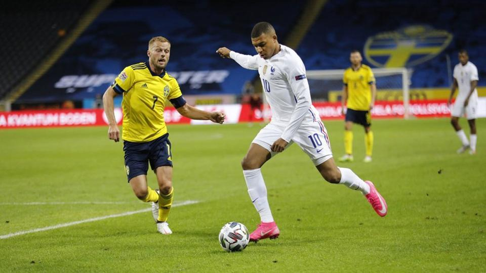France's Kylian Mbappe, right, scores a goal, and to the left, Sweden's Sebastian Larsson, in action during the UEFA Nations League football match