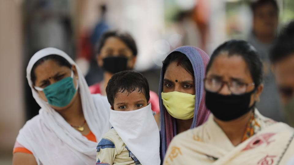 People wait in a queue to give their nasal swab samples to test for Covid-19 in Prayagraj.