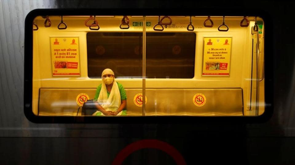 A woman wearing a face mask travels inside a Delhi metro train, on the first day of the restart of their operations, amidst the spread of coronavirus disease (COVID-19), in New Delhi.