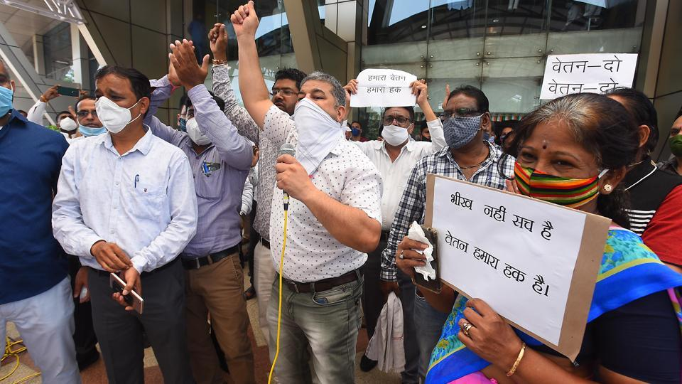 Aam Aadmi Party supporters and MCD employees raise slogans during a protest against the non payment of salaries of MCD employees outside Civic Center, in New Delhi.