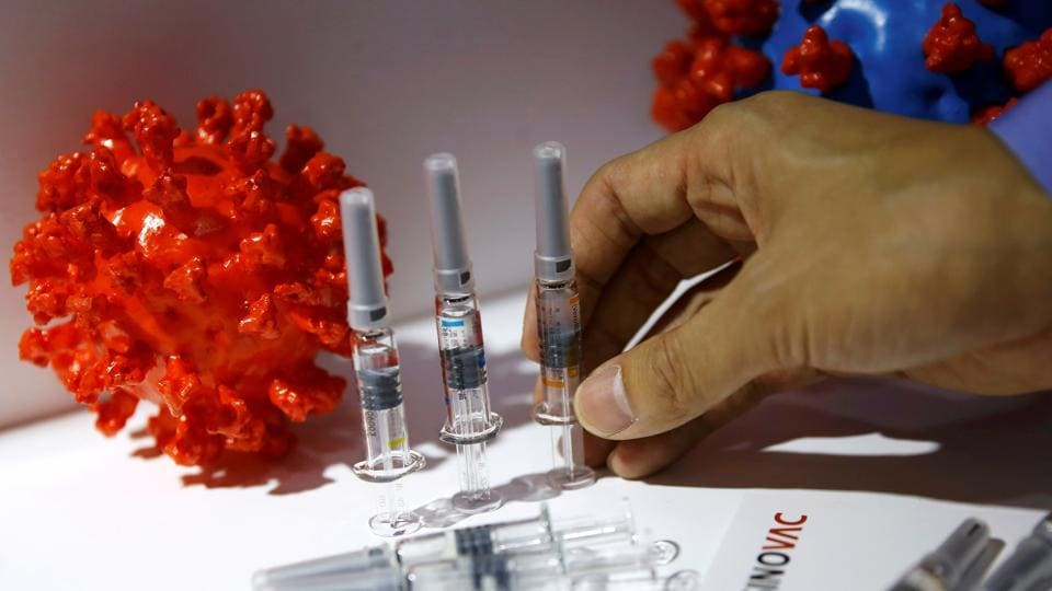 A staff member places a coronavirus vaccine candidate from Sinovac Biotech Ltd at its booth for display during the 2020 China International Fair for Trade in Services (CIFTIS).