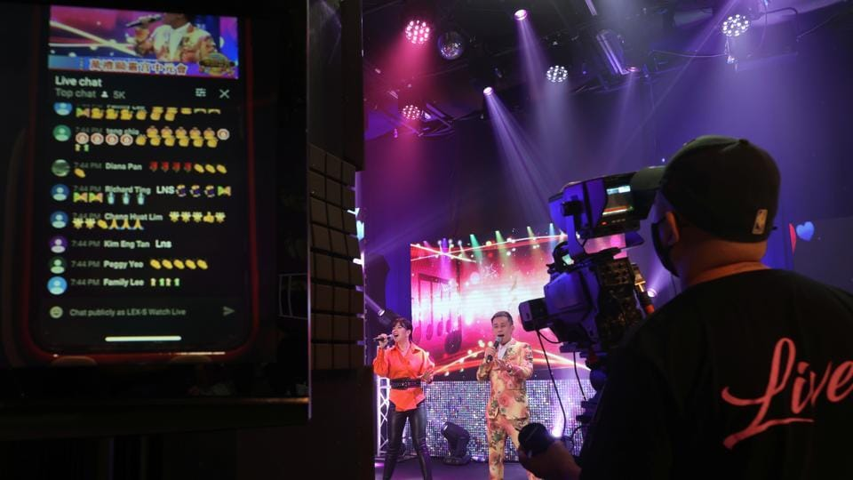Live comments from viewers are displayed on a screen as getai Singapore Febe Huang and Leon Lim perform at a live streaming getai show at a studio in Singapore September 5, 2020. The coronavirus disease (COVID-19) outbreak has prompted Getais, or free concerts that are traditionally staged outdoors for the living and the dead during the Hungry Ghost Festival, to go virtual.