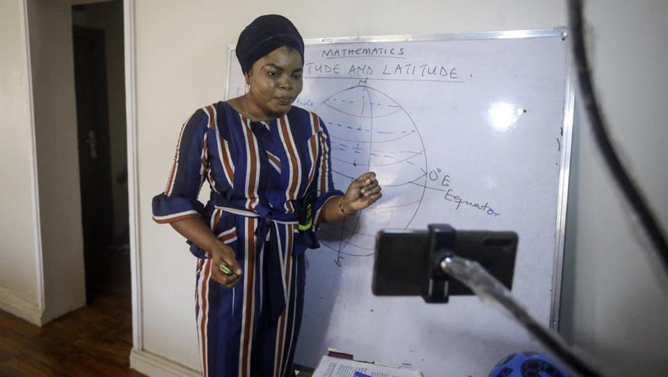 Mathematics teacher Basirat Olamide Ajayi, 36, teaches longitude and latitude online via her mobile phone from her house in Lagos, Nigeria.
