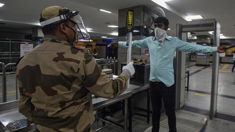 A security official wearing a face-shield frisks a commuter at Model Town Metro Station in New Delhi.