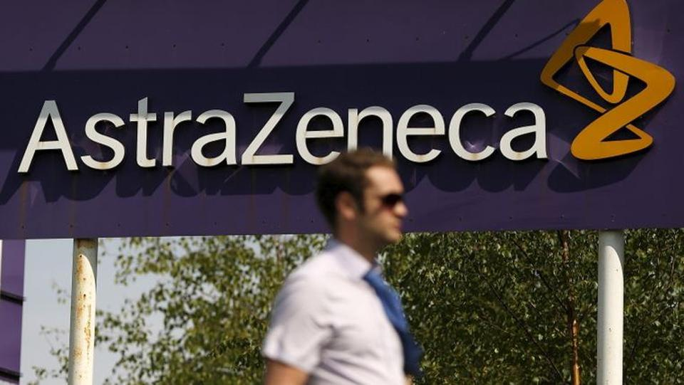 A man walks past a sign at an AstraZeneca site in Macclesfield, central England