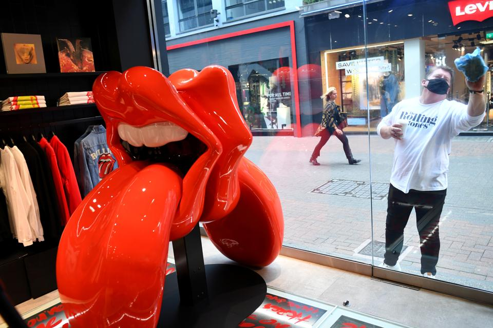 A shop assistant cleans a window of the new flagship Rolling Stones store named 'RS No. 9 Carnaby' in London, Britain, September 8, 2020.  (REUTERS)