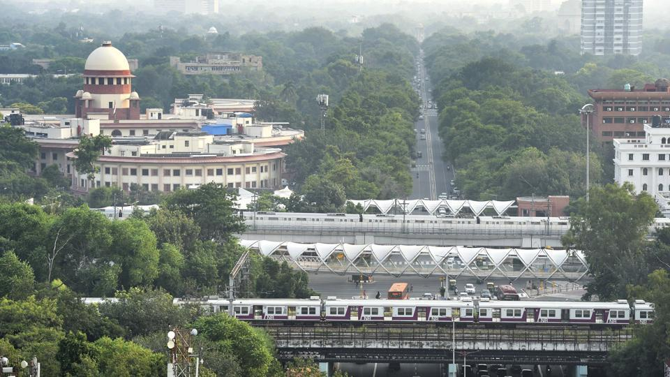 A Blue Line Metro train (back) passes an Indian Railways train on an elevated track near ITO in New Delhi.