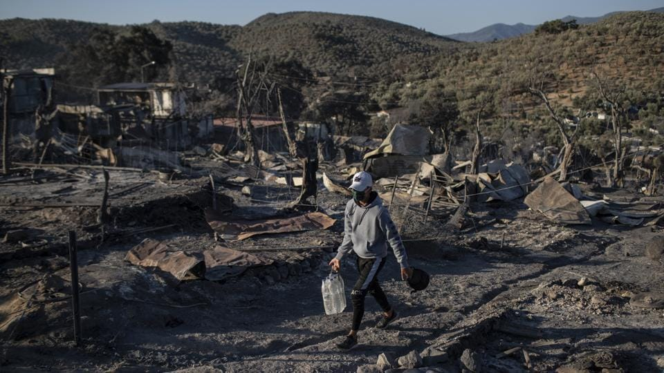 A migrant carries water along the Moria refugee camp in Lesbos, Greece on September 10. Early morning saw former residents of the camp, which had been under coronavirus lockdown, return to the area to pick through the charred remains of their belongings, salvaging what they could. (Petros Giannakouris / AP)