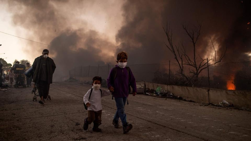 Two children leave after the second fire broke out in the Moria migrants camp on September 9. Greek authorities transferred 406 unaccompanied minors to safe locations the mainland early on September 10, the Greek Prime Minister's office said. (Angelos Tzortzinis / AFP)