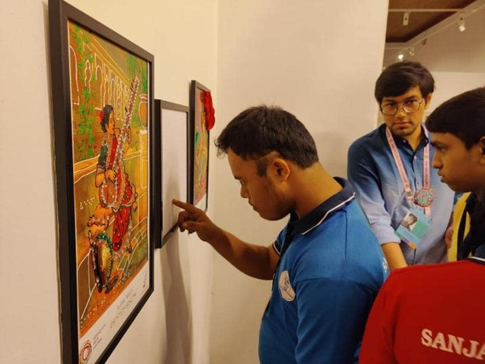 A differently abled student reads Braille art and signage at the Serendipity Arts festival in Goa in 2019.