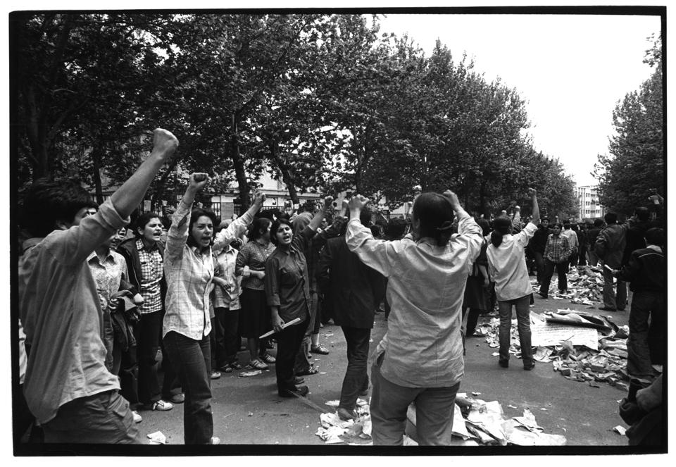 Female leftist students chant anti oppression slogans while standing in rows with piles of newspapers and cardboard ready to burn in case of tear gas attack by Revolutionary Guards, before street clashes with Hezbollah forces broke outside Tehran university campus, on the occasion of Cultural Revolution, 21st April 1981. The Cultural Revolution (1980-1987) was a period following the 1979 Islamic Revolution in Iran where the academia of Iran was purged of Western and non-Islamic influences to bring it in line with Shia Islam. The official name used by the Islamic Republic is