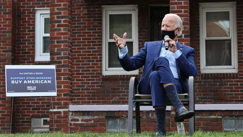 Wearing a face mask to reduce the risk posed by the coronavirus, Democratic presidential nominee Joe Biden talks with members of the United Steelworkers union in a supporter's back yard (AFP)