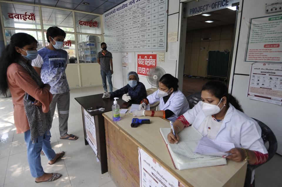 Health workers register people for coronavirus testing, at Sector 30 District Hospital, in Noida.