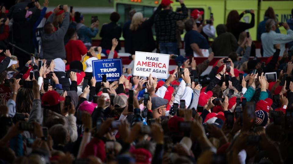Attendees hold signs during a campaign rally with U.S. President Donald Trump in Freeland, Michigan, US (Bloomberg)