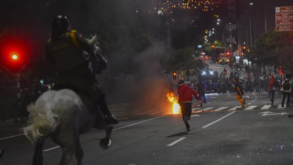 Demonstrators run as police on horses chase them during a protest against police brutality in Medellin, Colombia on September 10. At least 10 people were killed and hundreds wounded after rioting broke out in the Colombian capital Bogota during protests over the death of a man repeatedly tasered by police. (Joaquin Sarmiento / AFP)