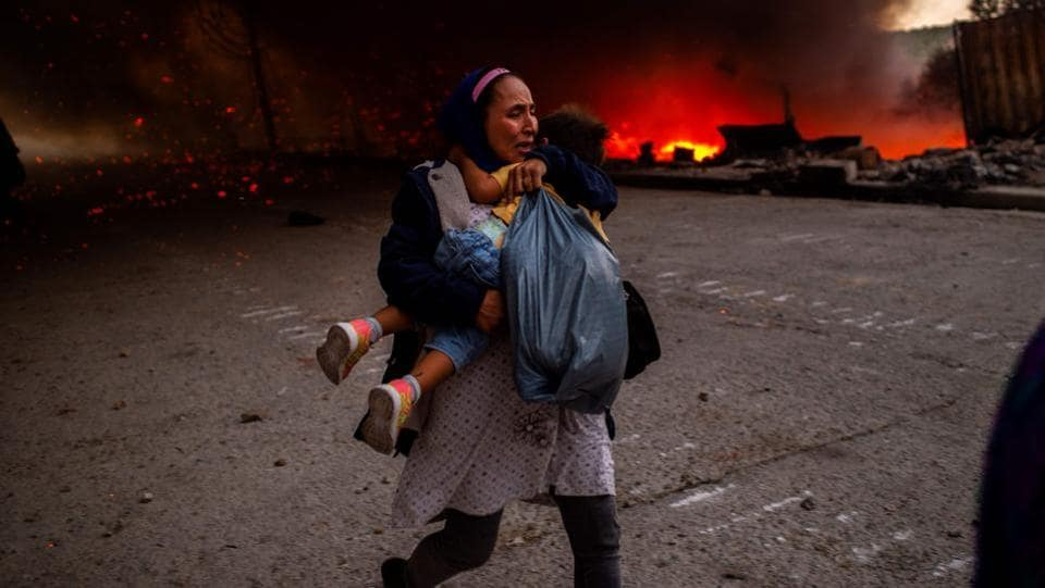 A woman flees with a little girl in front of a fire burning in the Moria camp for migrants on the Greek island of Lesbos on September 9. Thousands of asylum seekers escaped in panic and are camping in the open after two fires ripped through the camp of Moria, the country's largest and most notorious migrant facility. (Angelos Tzortzinis / AFP)