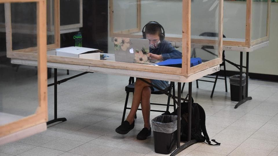 A student follows along remotely with their regular school teacher's online live lesson from a desk separated from others by plastic barriers at STAR Eco Station Tutoring & Enrichment Center on September 10, in Culver City, California. A lawsuit brought by the Orange County Board of Education seeking to compel the state of California to reopen public schools was shot down by the California Supreme Court on September 10. (Robyn Beck / AFP)