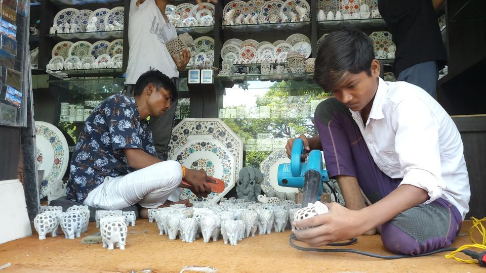 Staff at a shop in Agra arranging marble products after the date of the reopening of the Taj Mahal was announced.
