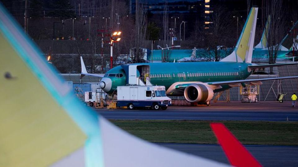 A service truck is seen stopped next to a Boeing 737 Max aircraft in storage at the Renton Municipal Airport in Renton, Washington.