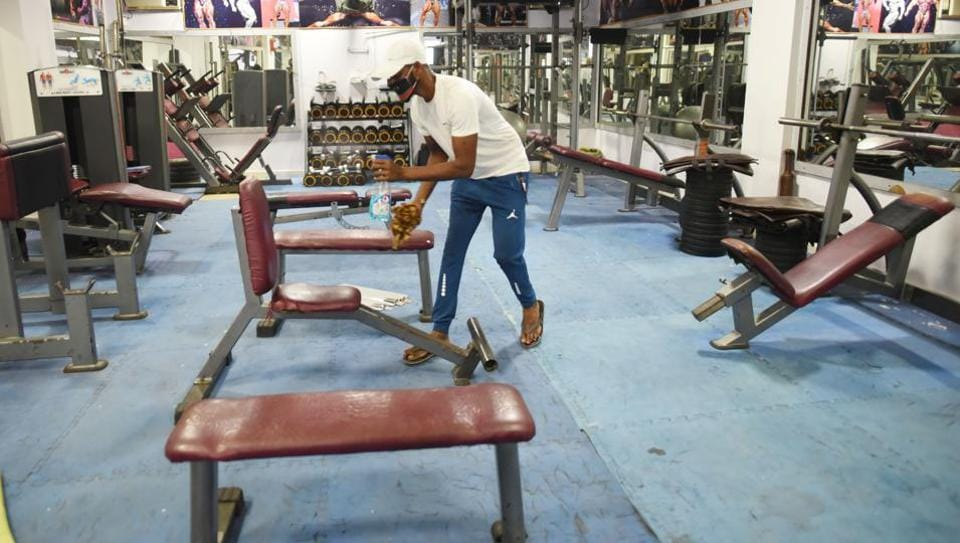 Staff cleaning and sanitising equipment and premises of a gym.