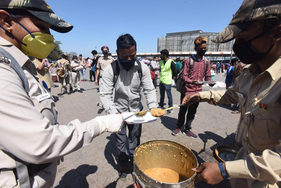 Civil defence personnel offer food to migrant workers heading home, Anand Vihar Bus Terminus, Delhi, March 28, 2020