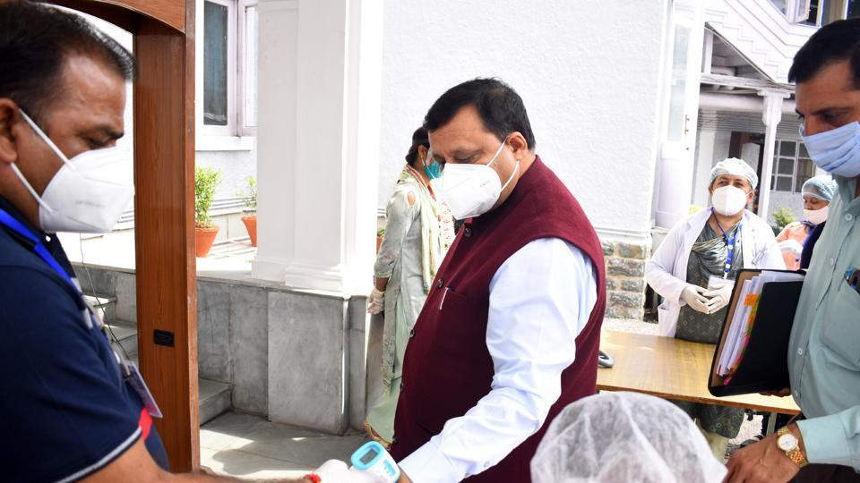 Security personnel check the body temperature of rural development and panchayatiraj minister Virender Kanwar before going to attend the monsoon session in Shimla on Monday.