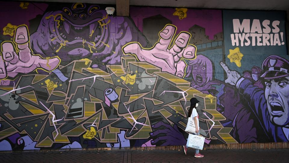 A pedestrian wearing a face mask walks past graffiti in Birmingham, central England on September 14 after the British government imposed fresh restrictions on the city after a rise in cases of the novel coronavirus.