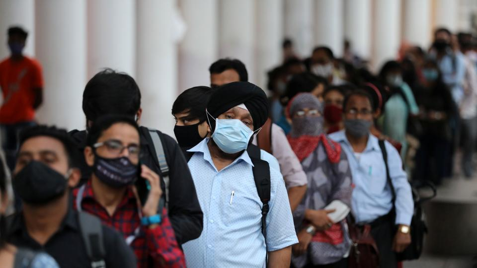 People wearing face masks stand in a line to enter a metro station during Covid-19, in New Delhi on Monday.
