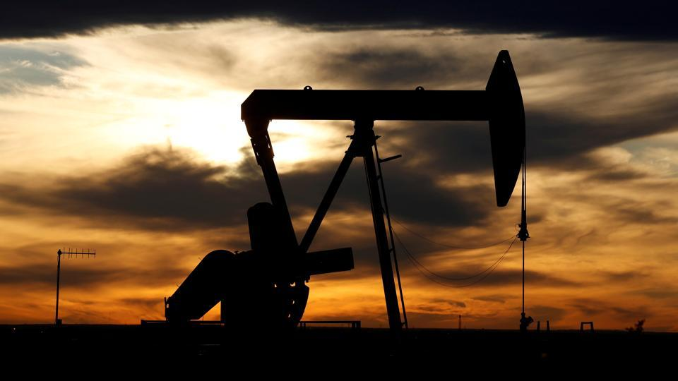 The sun sets behind a crude oil pump jack on a drill pad in the Permian Basin in Loving County, Texas, US.