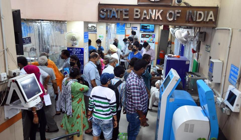 People crowd at the entrance of a State Bank of India branch while waiting to make transactions, at Laxmi Nagar, in New Delhi (Photo by Raj K Raj/ Hindustan Times)