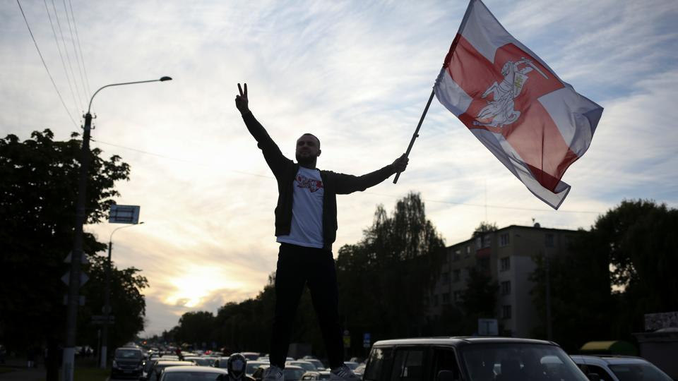 A protester with a historical white-red-white flag of Belarus stands on top of a car during a rally against police brutality following protests to reject the presidential election results in Minsk, Belarus September 13, 2020.